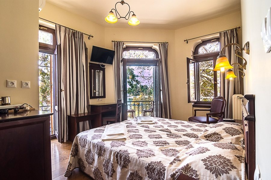 Δίκλινο πολυτελές δωμάτιο με μπαλκονόπορτες και παράθυρα και τηλεόραση